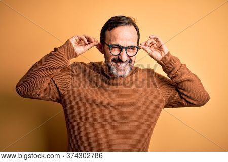 Middle age hoary man wearing brown sweater and glasses over isolated yellow background Smiling pulling ears with fingers, funny gesture. Audition problem