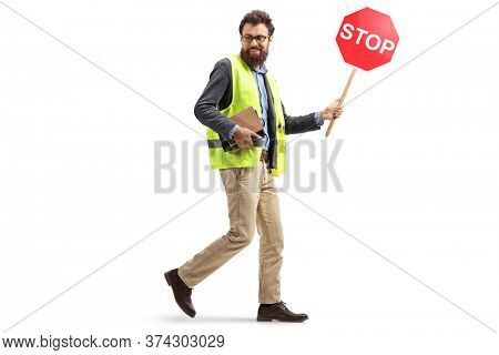 Full length shot of a bearded man in a safety vest walking with a stop traffic sign and looking behind isolated on white background