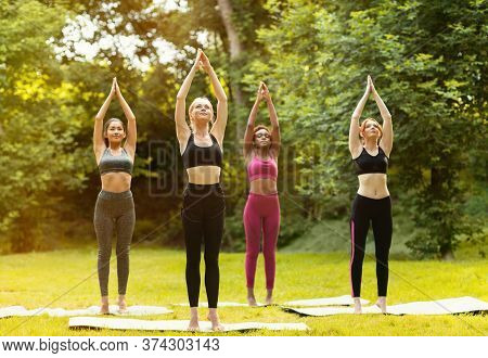 Millennial Women Of Different Races Enjoying Their Morning Yoga Practice Outdoors
