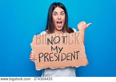 Young beautiful woman on disagreement holding banner with not my president message pointing thumb up to the side smiling happy with open mouth