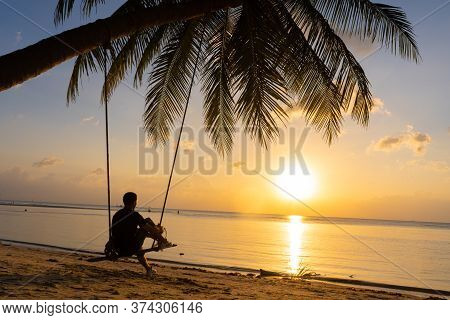 The Guy Enjoys The Sunset Riding On A Swing On The Ptropical Beach. Silhouettes Of A Guy On A Swing