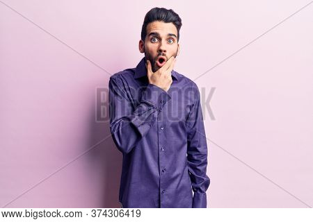 Young handsome man with beard wearing casual shirt looking fascinated with disbelief, surprise and amazed expression with hands on chin