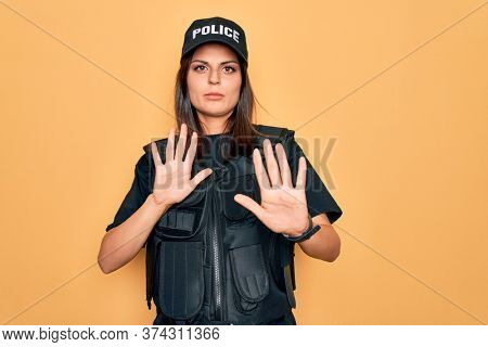 Young beautiful brunette policewoman wearing police uniform bulletproof and cap Moving away hands palms showing refusal and denial with afraid and disgusting expression. Stop and forbidden.