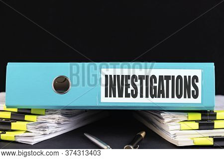 Investigations Text Is Written On A Folder Lying On A Stack Of Papers On An Office Desk. Business Co