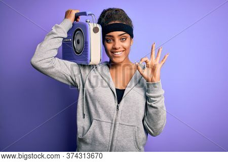 Young african american afro girl listening to music holding vintage radio over purple background doing ok sign with fingers, excellent symbol