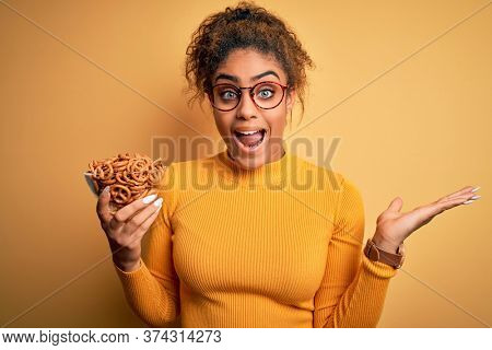 African american afro girl holding bowl with german baked pretzels over yellow background very happy and excited, winner expression celebrating victory screaming with big smile and raised hands