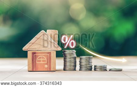 House And Coins Place On The Wood Table Is Ladder With White Illustration Shows Decreasing Of Intere