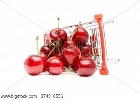 Closeup Of Sweet Cherries In A Miniature Toy Shopping Trolley Isolated On White Background. Fresh Fr