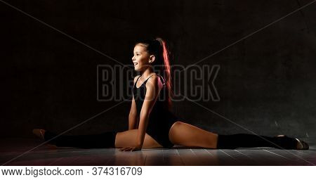 Smiling Girl Gymnast In Black Sport Body And Special Shoes Sitting In A Twine Face Forward Over A Da
