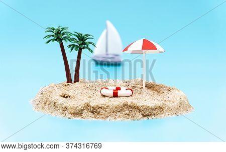 Miniature Toy Island With Palm Trees, Sun Umbrella, A Lifebuoy And A Sailboat On A Light Blue Backgr