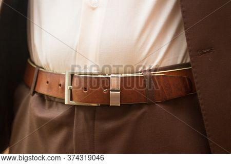 Man Wears Belt. Close-up Of Male Waist On Brown Leather Belt