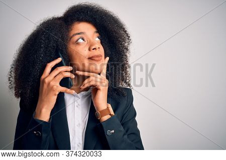 Young african american business woman with afro hair calling using smartphone mobile serious face thinking about question, very confused idea