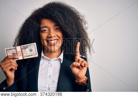Young african american business woman with afro hair holding a bunch of cash dollars banknotes surprised with an idea or question pointing finger with happy face, number one