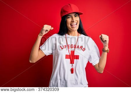 Young beautiful hispanic lifeguard woman wearing safeguard t-shirt and whistle celebrating surprised and amazed for success with arms raised and open eyes. Winner concept.