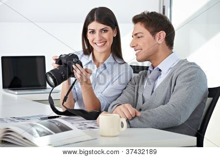 Photographer with assistant holding camera in their office