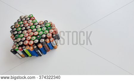 Many Alkaline Batteries In The Shape Of A Heart On White Background. Concept Of Recycling Waste And
