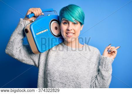 Young woman with blue fashion hair listening to music holding vintage portable radio very happy pointing with hand and finger to the side