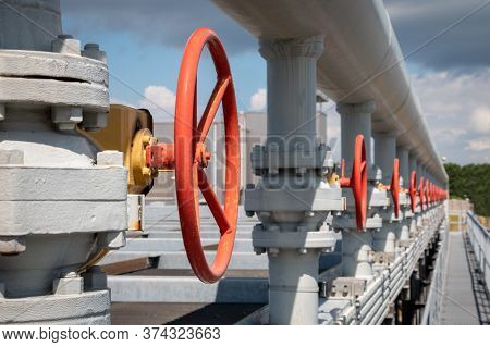 Red Manual Valves For Opening Or Closing A Pipe, Also Called Hand Valve In An Industrial Area