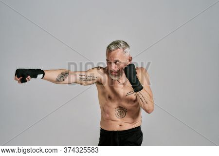 Half Naked Middle Aged Athletic Man, Kickboxer Looking Aside While Boxing, Practicing Punches In Stu