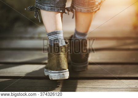 The Slender Legs Of A Woman In Rough Boots, Grey Jeans And Socks, Walking Carelessly Along A Wooden