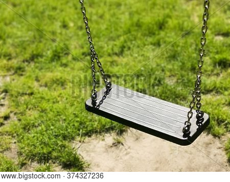 Empty Swing On Children Playground. Green Grass Background. Vacant Chain Swing For Kids In A Park. C