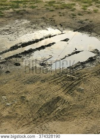 Puddles In Rainy Day. Muddy Field, Dirt Road After Rain. Puddle And Mud With Tire Track Texture. Imp
