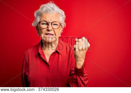 Senior beautiful grey-haired woman wearing casual shirt and glasses over red background angry and mad raising fist frustrated and furious while shouting with anger. Rage and aggressive concept.