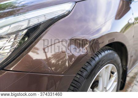 A Dent In A Brown Car. Brown Metallic
