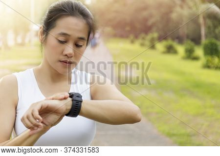 Asian Woman Setting Up The Fitness Smart Watch For Running. Young Women Checking Watch Device. Women