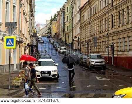 Moscow, Russia - July 8, 2018: Pedestrians On A Pedestrian Crosswalk In The Rain