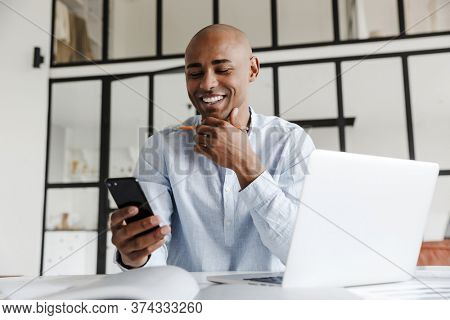 Photo of laughing african american man using mobile phone while working with laptop at table in living room