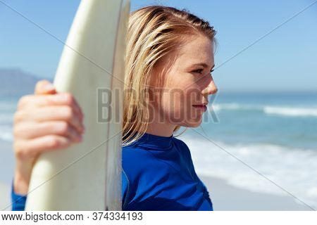 Attractive blonde Caucasian woman enjoying time at the beach on a sunny day, holding a surfboard and smiling, with blue sky and sea in the background. Summer tropical beach vacation.