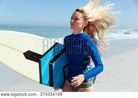 Attractive blonde Caucasian woman enjoying time at the beach on a sunny day, holding surfboard and running, with blue sky and sea in the background. Summer tropical beach vacation.