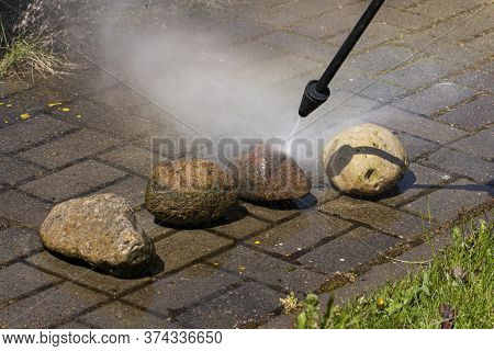 Sprayer Of High-pressure Washer Cleans Stones Close Up On Garden Line Of Country House. Spring Clean