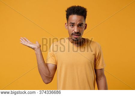Perplexed Young African American Guy In Casual T-shirt Posing Isolated On Yellow Orange Background S