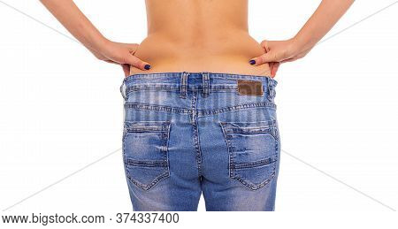 Losing Weight. Slender Girl In Big Jeans On A White Background.