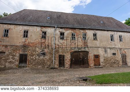 An Old Abandoned And Dilapidated Peasant House. The Weather Caused The House To Become A Ruin