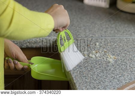 Girls Hands Sweeping Garbage Bread Crumbs Off Gray Kitchen Table Close Up. House Cleaning Concept. S