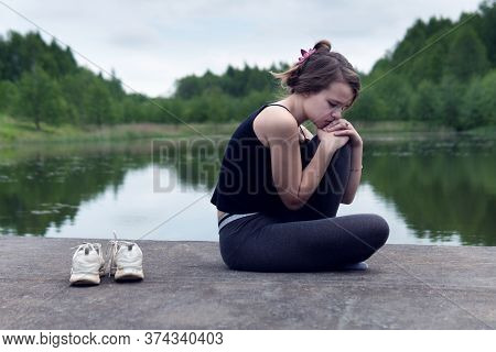 Sad Teen Girl Sits On Pond Pier In Cloudy Summer Morning