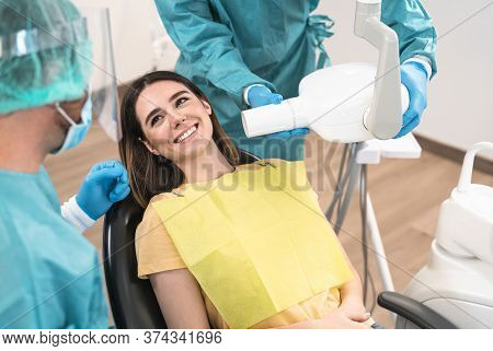 Man Dentist Operating Young Smiling Woman In Dental Clinic - Oral Healthcare Assistance Concept