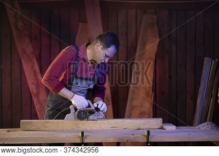 Middle-aged Male Craftsman Processes Wooden Workpiece With Electric Planer On Workbench At Country H