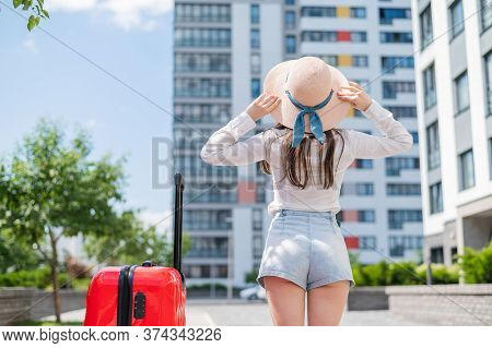 A Girl In Shorts And A Hat Stands Back With A Red Suitcase Outside. A Young Woman Is Walking With Lu