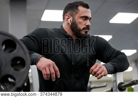 Strong Young Caucasian Man With Beard During Recreation Pause In Sport Workout In Gym