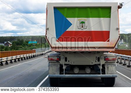 Big  Truck With The National Flag Of Equatorial Guinea  Moving On The Highway, Against The Backgroun