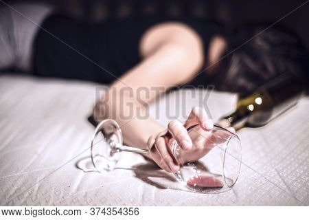 A Young Girl Suffering From Chronic Alcoholism Lies In A Dirty Room, Next To A Bottle Of Wine And A
