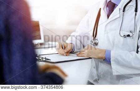 A Doctor Is Writing A Medical Prescription For His Patient, While Sitting Together At The Desk In Th