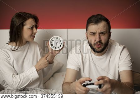Young Couple Having Quarrel In Bedroom Due To Gambling Addiction. Excited Man With Joysticks In Hand