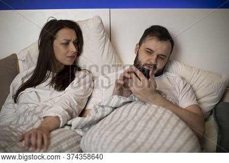 Young Married Couple Laying In Bed, Handsome Man Using Mobile Phone Checking Social Network Ignoring