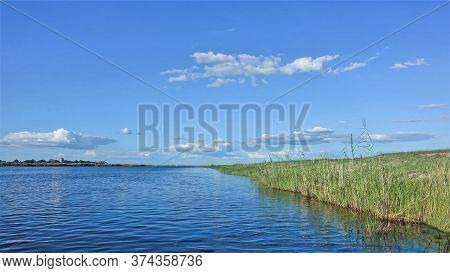 Peaceful Landscape Of Africa. Sunny Summer Day. The Blue River Flows Calmly, Green Grass Grows On Th