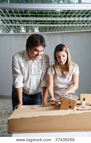 Young male architect standing beside colleague working on model house